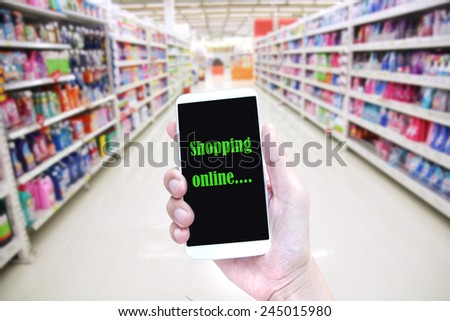hand hold smartphone in supermarket , shopping online - stock photo