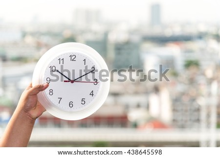 hand holding a clock on blurred background city  - stock photo