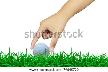 Hand holding a golf ball on green grass