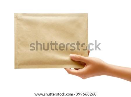 Hand holding envelope. Studio photography of woman's hand holding yellow envelope - stock photo