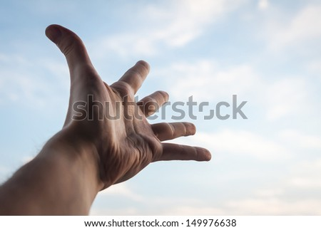 Hand of a man reaching to towards sky.  - stock photo