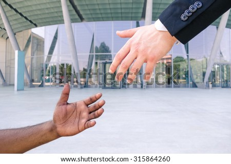 Hand of young american businessman reach out black refugee arm - Humanitarian aid against racism - Black and white hands reaching - Concept of European community aid to african people escape from war - stock photo
