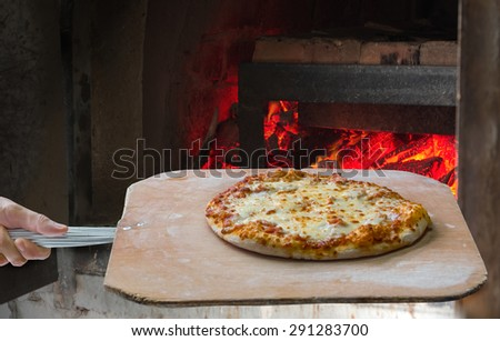 Hand pushing the finished pizza from the oven with the pizza shovel, Clipping path  - stock photo