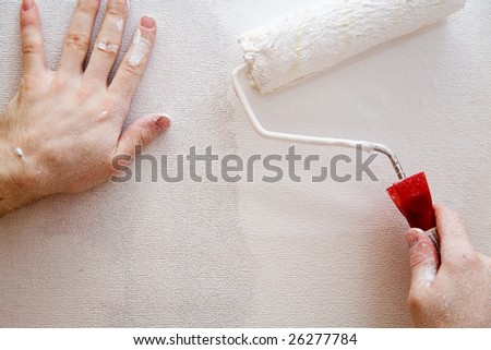 hand with a paint roller covered in white paint, painting over a white wall.
