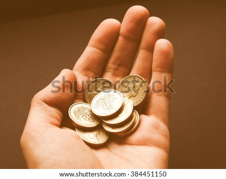 Hand with British Pounds coins (UK currency) over a dark background vintage