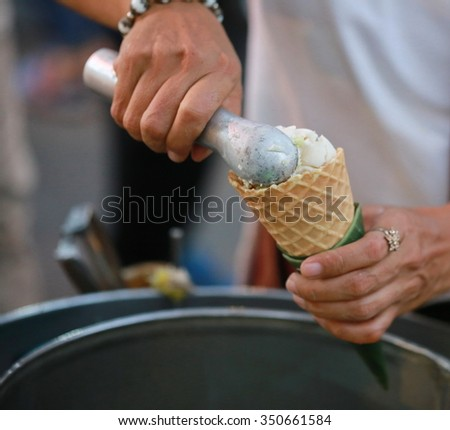 hand with ice cream scoop on cones , Thailand ,Vanilla ice cream scoop, scooped out of a container with a utensil - stock photo