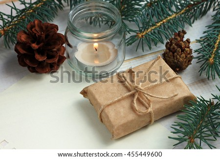 Handmade simple winter holiday decor, teacandle light in glass jar, pine boughs and cones, handcrafted gift wrap idea, empty note paper. Toned.   - stock photo