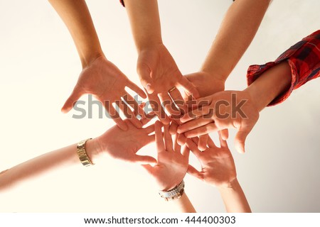 Hands close-up of friends joined together. The concept of friendship.