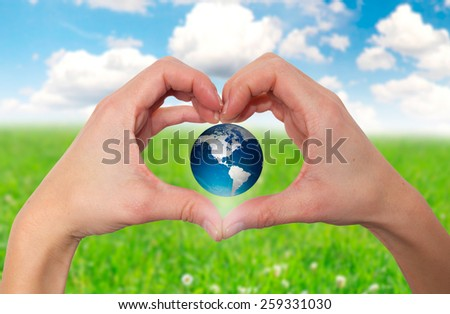 Hands holding green globe with grassy background - Stock Image - stock photo