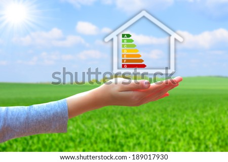 hands holding  house with energy efficiency rating  - stock photo
