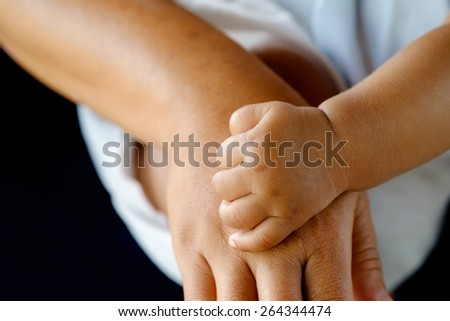 hands of mother and baby closeup - stock photo