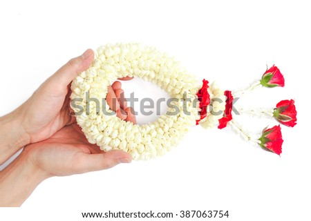 2 Hands receiving Flower Garland with jasmine & roses  (flower garland is widely given on Songkran festival & Mother's day in Thailand) isolated on white - stock photo