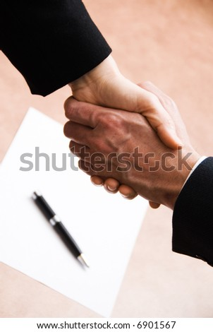 2 hands shaking with a blank contract and pen