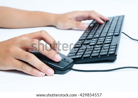 hands typing on keyboard and using mouse