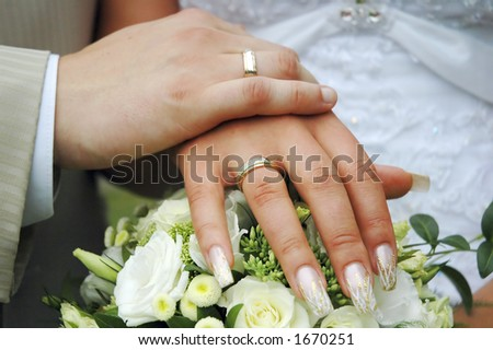2 hands with wedding rings on flowers