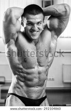 Handsome and strong man with beautiful body doing exercises in gym - stock photo