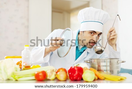 handsome chef tasting soup with ladle from pan - stock photo