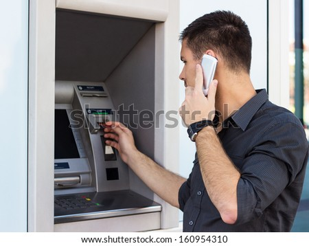Handsome man talking on the phone and put his credit card at the atm  - stock photo