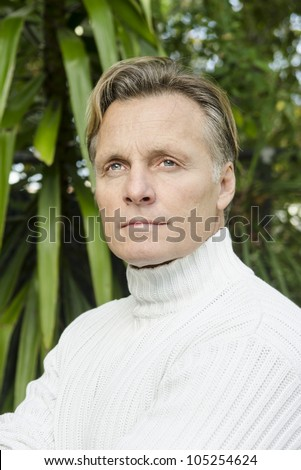 handsome mature blond man in his forties wearing a white sweater. - stock photo