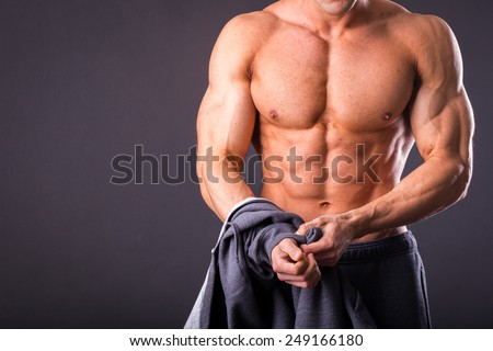 Handsome, muscular man in sportswear posing on a dark background. Confident man in an unbuttoned jacket. Bodybuilder man in  sports jacket. - stock photo