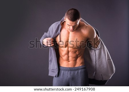 Handsome, muscular man in sportswear posing on a dark background. Confident man in an unbuttoned jacket. Bodybuilder man in  sports jacket.