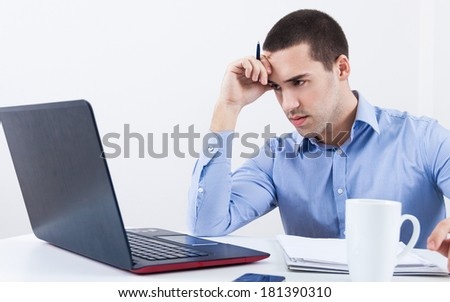 Handsome young man in shirt working on laptop while sitting at his working place