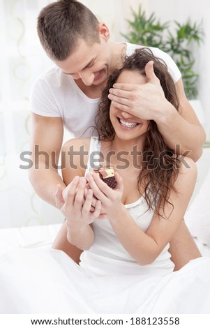 Handsome young man sitting on the bed and holding a gift box  covering his girlfriend  eyes with hands - stock photo