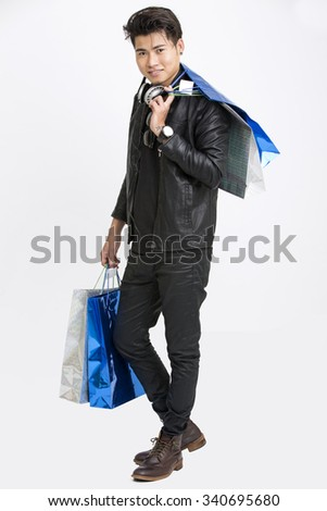 Handsome young man walking with shopping bags with head phone on white background. - stock photo