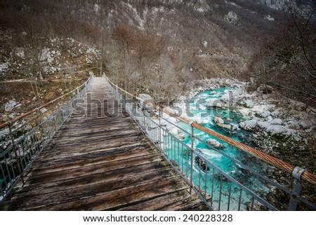 Hanging bridge over turquoise Soca river in the Triglav National Park in Slovenia.  - stock photo