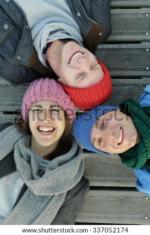 happy best friends funny faces, heads together lying down looking at the camera as posing for a selfie photo - youth friendship togetherness and joy concept international friends having fun. - stock photo