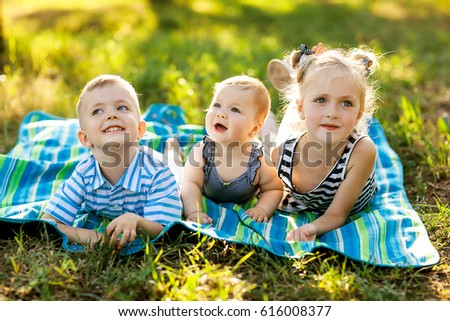 happy boys and girls lying on a green grass on picnic