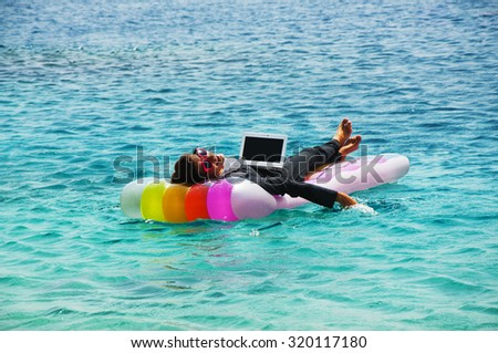 Happy businesswoman with laptop on floating mattress in red sea