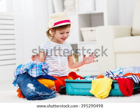 happy child girl tourist packs clothes into a suitcase for travel, vacation