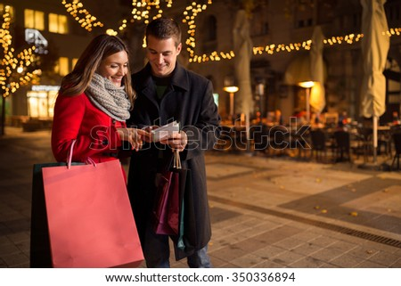Happy couple checking shopping list for Christmas on street  - stock photo