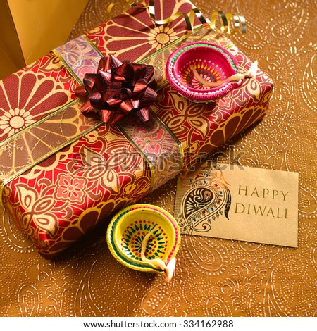 'Happy Diwali' message on a tag along with gift box and lamps. Indian festive background.  - stock photo