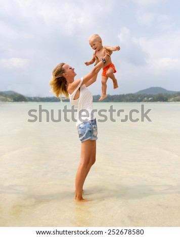 Happy family. Young mother throws up her baby in the sky on a sunny day. Photo of a mother and her little son playing on the beach. Positive human feelings and emotions.