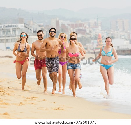 Happy friends running in swimwear at sea beach at sunny day