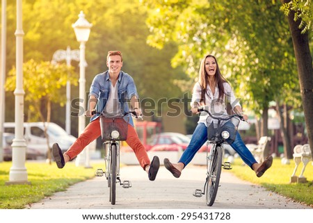 Happy funny young couple riding on bicycle - stock photo