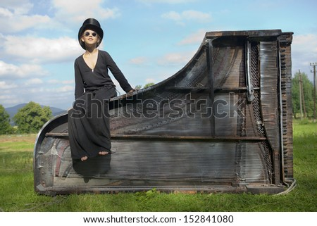 Happy girl in a round black glasses and a black top hat sits on a huge, old overturned black royale.Solnechny summer day green lawn. - stock photo