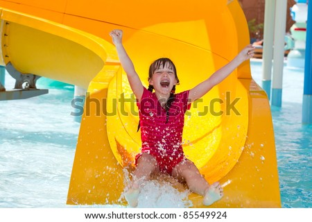 Happy girl on waterslide - stock photo