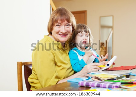 Happy grandmother plays with baby  in home interior - stock photo