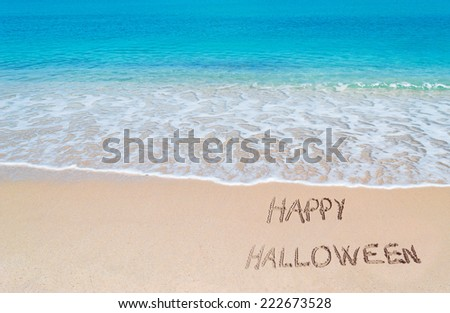 """happy halloween"" written on a tropical beach - stock photo"