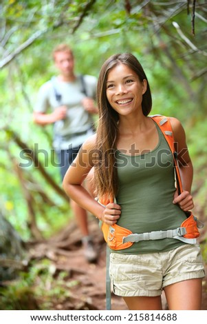 Happy hiker girl with backpack trekking in forest smiling. - stock photo