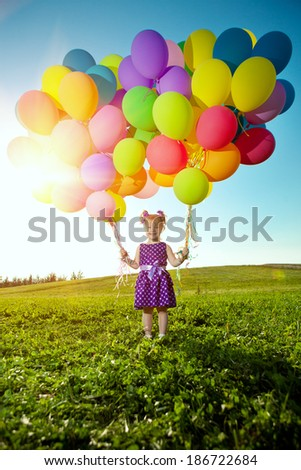 Happy little girl holding colorful balloons. Child playing on  green meadow. Smiling  kid. Portrait of baby outdoor  - stock photo