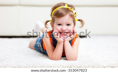 Happy little girl lying on the floor at home