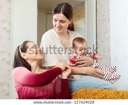 happy mature woman communicates with her adult daughter and granddaughter