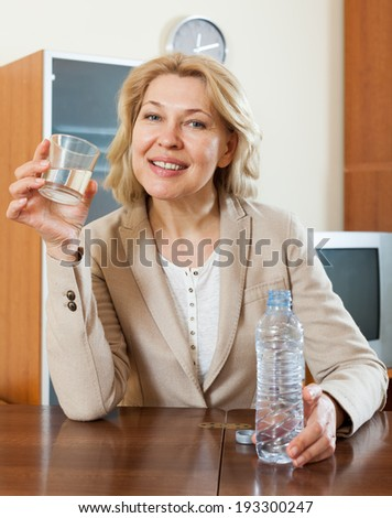 Happy mature woman drinking water from glass at home