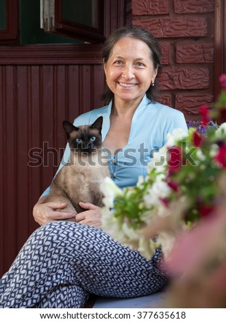 Happy middle-aged woman resting on   porch of   house.  - stock photo