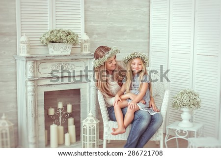 ? happy mother is kissing the hand of her young daughter. They are sitting in the armchair.They are having casual clothes and floral wreathes on. The atmosphere of happiness is all around them. - stock photo