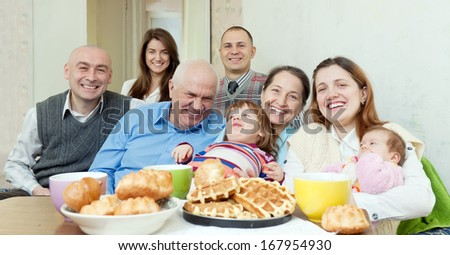 happy multigeneration family communicate around tea table at home - stock photo